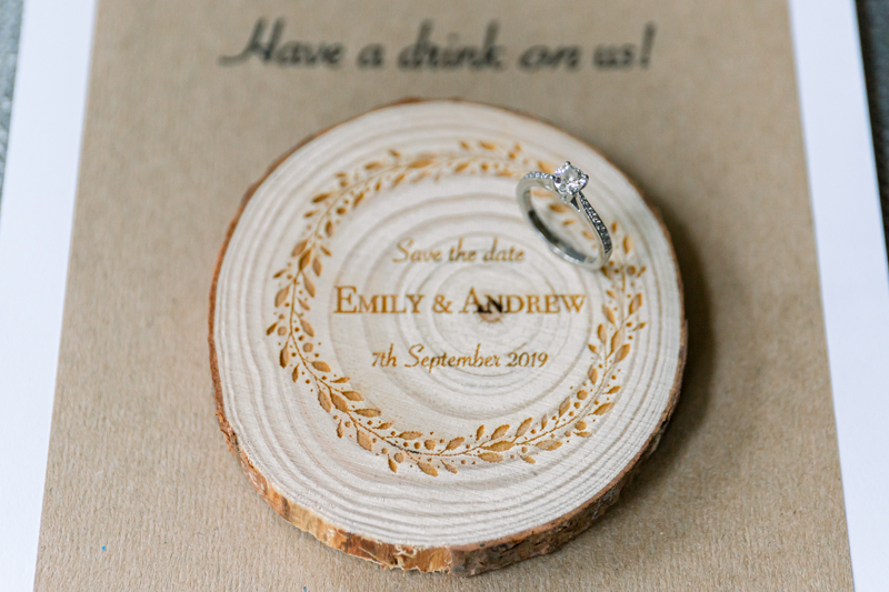 A moissanite engagement ring placed on a wooden placecard