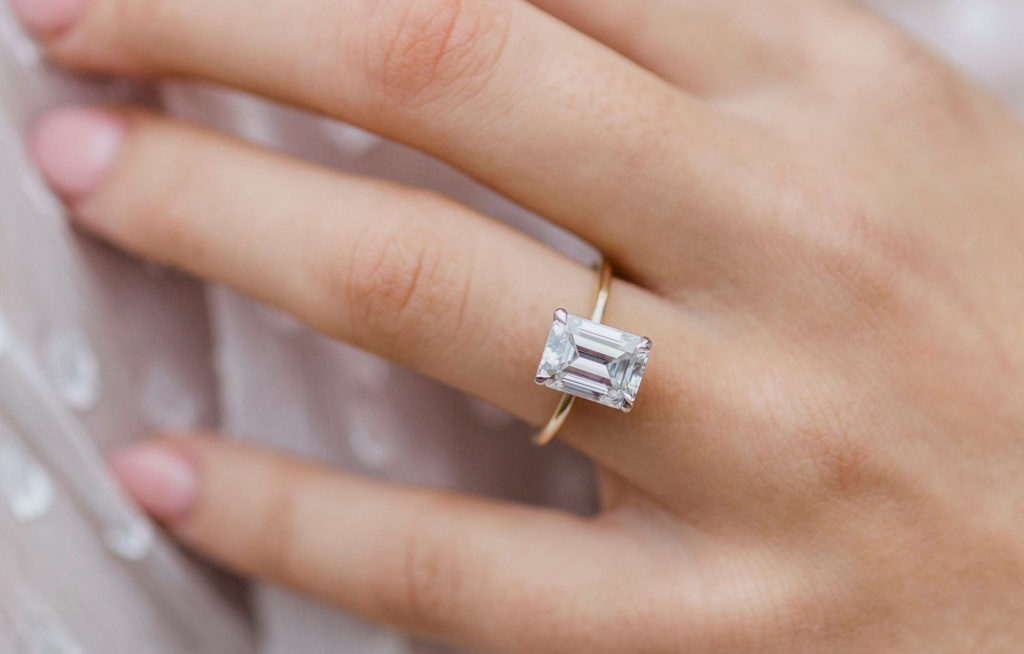 A stunning emerald cut moissanite engagement ring from East West Gem Co website